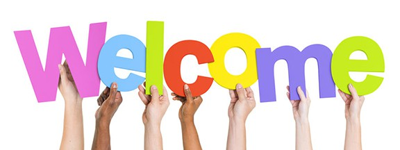 "Multi-ethnic group of hands holding up letters spelling out ""Welcome"""