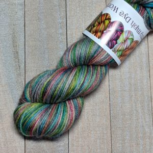a self-striping skein of yarn with a gray stripe and a variegated stripe of purple, blue, and green