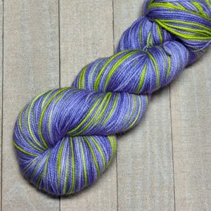 a two-stripe skein of self-striping yarn in vivid violet and lime green