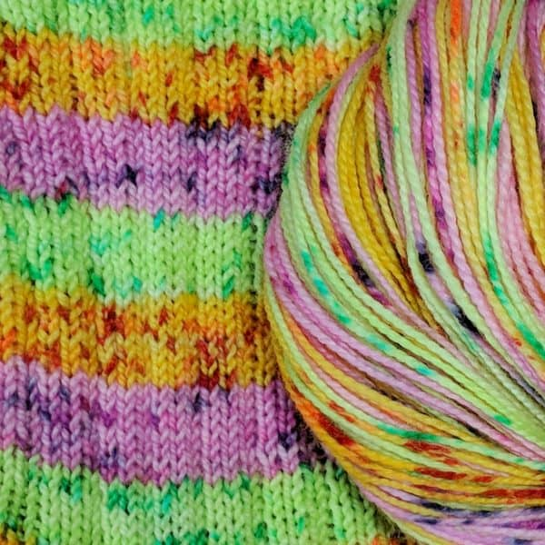 sample of a three stripe colorway of green, orange, and pink, with all stripes speckled in deeper shades of these colors