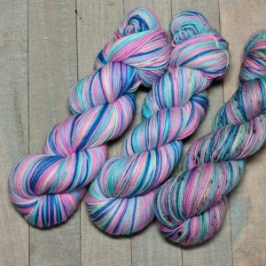 three skeins of self-striping yarn in shades of dark blue, light blue, magenta, and white