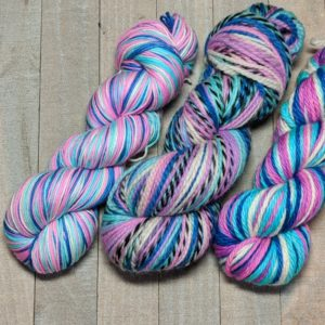 three skeins of self-striping yarn in shades of dark blue, bright blue, magenta, and white