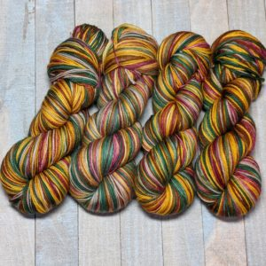 four skeins of a self-striping colorway in tan, green, brown, warm honey, and red