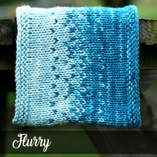 A two-toned blue colorwork cowl featuring a speckled colorwork motif hangs vertically from the edge of a picnic table.
