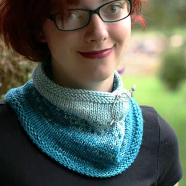 A gently smiling young woman with short red hair, wearing red lipstick, black framed glasses and a black shirt models a blue two-toned knitted cowl that features a speckled colorwork motif. It is folded over to be closer to her neck and is secured with a silver shawl pin.