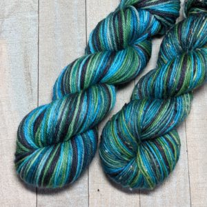 two skeins of self-striping yarn in black, peacock, turquoise blue and turquoise green