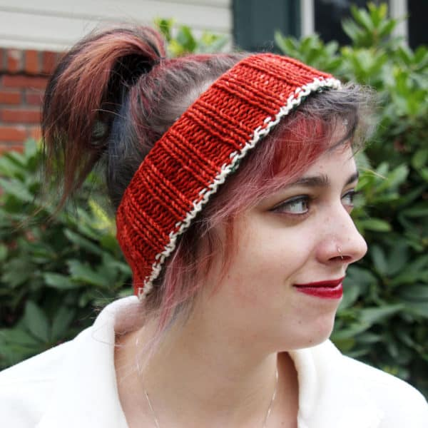 Young woman with reddish hair in a ponytail and red lipstick looking to the right out of the shot. She is wearing a striped knitted headband, the reverse side of the first photo, showing the iron oxide red half of the reversible headband with the white stripe still visible.