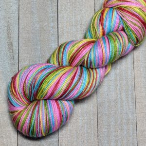 a skein of self-striping yarn in the pi sequence of stripes, five bright colors of pink, blue, yellow, red, and green