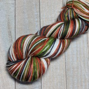 a five stripe skein of yarn in our pi stripe sequent in stripes of brown, green, white, reddish brown, and taupe