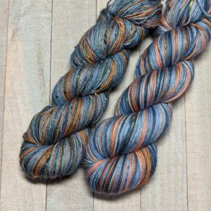 two skeins of self-striping yarn in light orange, blues, and peach with pops of yellow throughout