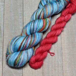 a skein of mostly blue self-striping with other bright stripes through, paired with a deep red mini skein