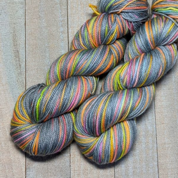 two skeins of self-striping yarn featuring a gray stripe with smaller brightly variegated stripes