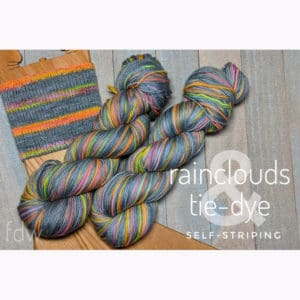 two skeins of self-striping yarn and a knit sample featuring a gray stripe with smaller brightly variegated stripes