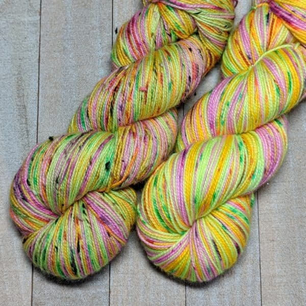two skeins of self-striping yarn, three stripes in bright colors of pink, green, and orange, all stripes are speckled as well