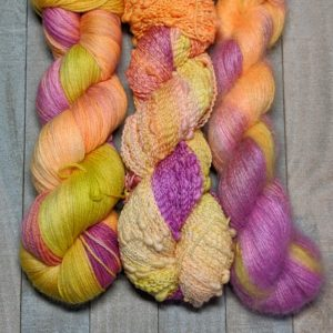 three skeins of yarn all dyed in bright warm tie-dye colors of magenta, bright orange, and pickle juice
