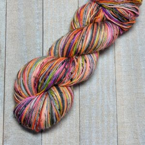 a skein of self-striping yarn with gray stripes and a highly speckled stripe of bright colors on a tweed yarn base