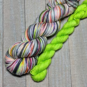 a three stripe self-striping skein of yarn with two varying gray stripes and a wide speckled stripe of bright colors in between them. Paired with a toxic green mini.